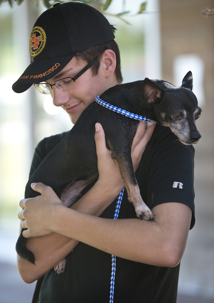 Kyle Fahs, 15, visits with Hector, a 10-year-old Miniature Pinscher en route to a new home.